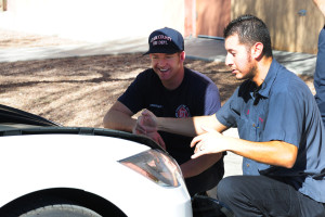 Tesla Motors Service Technician Jose demonstrates traction battery disconnection points on Tesla Motors Model S to firefighter.